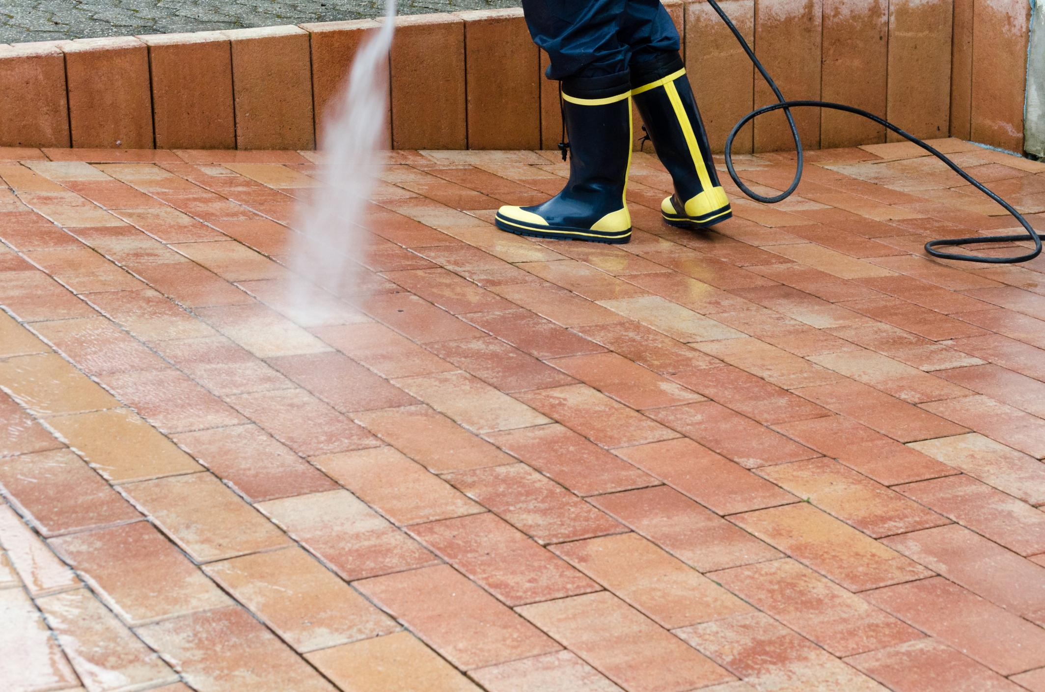 Worker pressure cleaning the ground